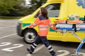 Blurry paramedics pulling gurney ambulance car — Stock Photo