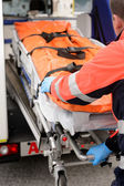 Paramedic rolling out gurney from emergency truck — Stock Photo