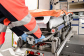 Paramedic pulling out gurney from ambulance car — Stock Photo