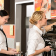 Two waitresses serving coffee with machine - Stockfoto