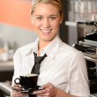 Young smiling waitress with cup of coffee — Stock Photo #24956887