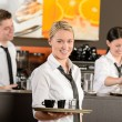 Confident waitress serving coffee with tray — Stockfoto