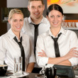Three server posing in uniform in cafe — Foto Stock