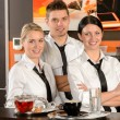 Three server posing in uniform in cafe — Stok fotoğraf