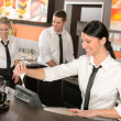 Foto Stock: Female cashier giving receipt working in cafe