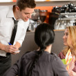 Stock Photo: Waiter taking orders from young woman customer