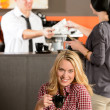 Happy female customer drinking espresso in cafe — Stockfoto