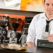 Handsome smiling male waiter giving receipt CZK — Stockfoto