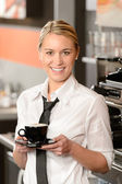 Young smiling waitress with cup of coffee — Stock Photo