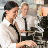 Female barista operating coffee maker machine — Stok fotoğraf
