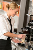 Attractive waitress making coffee with machine — Stock Photo