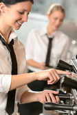 Smiling women waitress preparing coffee machine — Stock Photo