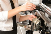 Barista steaming milk for hot cappuccino — Stock Photo