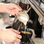 Kelnerka ręce wlewając mleko co cappuccino — Zdjęcie stockowe