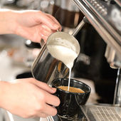Waitress hands pouring milk making cappuccino — Stok fotoğraf