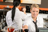 Young waitress cashier giving coffee in cafe — Stock Photo