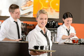 Confident waitress serving coffee with tray — Stock Photo