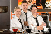 Three server posing in uniform in cafe — Stock Photo