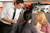 Waiter taking orders from young woman customer — Stock Photo
