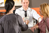 Female customers paying by cash USD bar — Stock Photo
