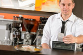 Handsome smiling male waiter giving receipt CZK — Stock Photo