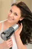 Happy girl blow drying her hair — 图库照片