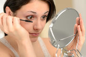 Attractive woman using mascara and handheld mirror — Stock Photo