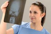 Doctora examinando radiografía con calavera — Foto de Stock
