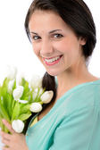 Cheerful young woman with bouquet of tulips — Stock Photo