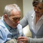 Nurse helping senior sick man with drinking — Stock Photo