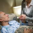 Old woman taking care of sick husband — Foto Stock