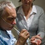 Caring senior wife holding drugs for husband — Stock Photo