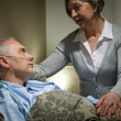 Worried senior woman caring with sick husband - Stock Photo