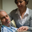Caring nurse with sleeping senior male patient — Stock Photo
