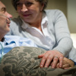 Elderly couple holding hands lying in bed — Stock Photo