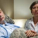 Caring wife holding sick senior husband's hands — Stock Photo
