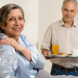 Caring senior man bringing breakfast to wife — Stock Photo