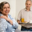 Stock Photo: Caring senior man bringing breakfast to wife
