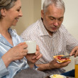 Elderly couple eating romantic breakfast in bed — Stock Photo