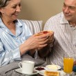 Senior couple having romantic morning breakfast — Stock Photo