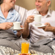 Mature couple enjoying breakfast at hotel room — Stock fotografie