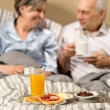 Pensioners drinking coffee in the bed — Stock Photo