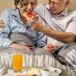 Senior man feeding breakfast to woman - Stock Photo