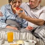 Senior man feeding breakfast to woman — Stock Photo