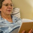 Aged woman reading book in residential home - Stock Photo