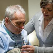 Enfermera ayudando a senior hombre enfermo con la bebida — Foto de Stock
