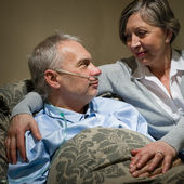 Ill old man lying bed with wife — Stock Photo