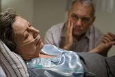 Chory starsza kobieta, leżąc w łóżku — Zdjęcie stockowe