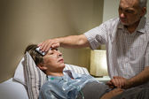 Caring senior man helping his sick wife — Stock Photo