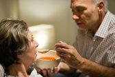 Caring senior man feeding his sick wife — Stock Photo